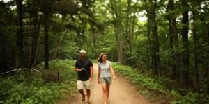 couple walking in woods smiling